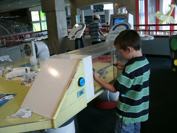 Issac is messing with some sort of wind-tunnel / paper airplane exhibit.