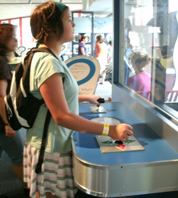 This is another flight exhibit that combines airfoil with blowing air to explain how airplanes work. The sign behind Rachel says Roll, Pitch, Yaw.