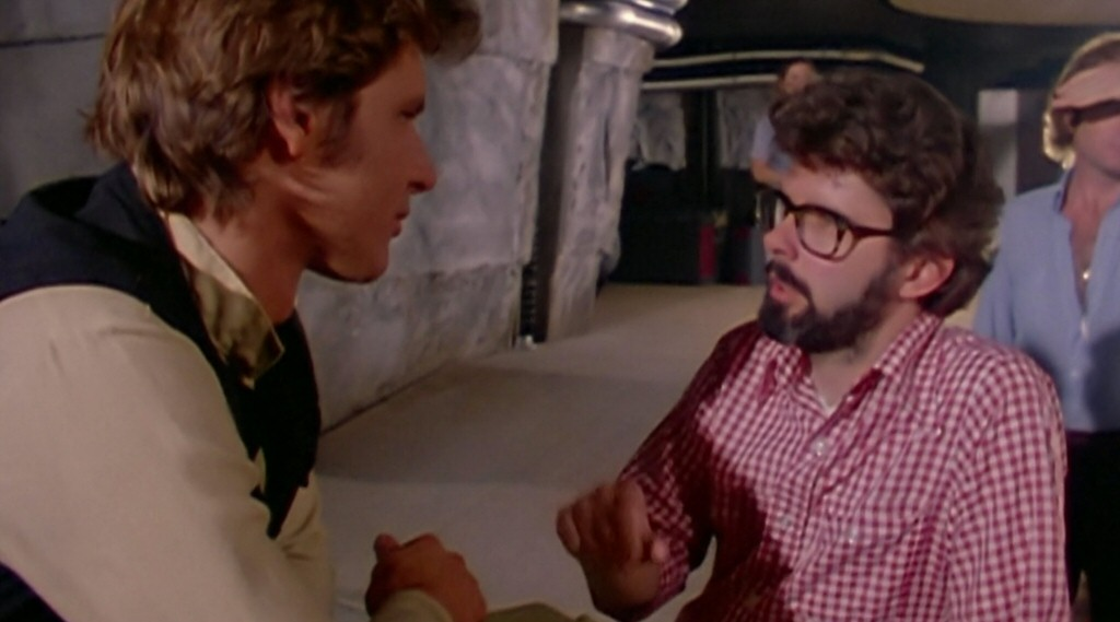 George Lucas on set with Harrison Ford, probably discussing how to deal with the constant clunking sound the dialog was making.